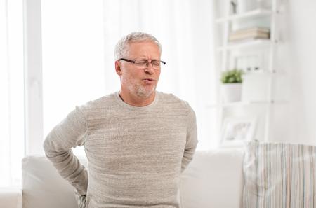 Infeliz hombre mayor que sufre de dolor de espalda en casa