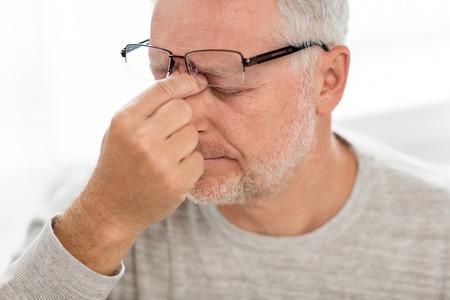 senior man in glasses massaging nose bridge
