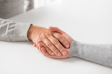 close up of young woman holding senior man hands Zdjęcie Seryjne