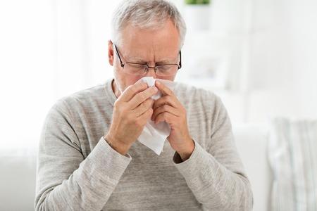 Kranker älterer Mann mit Papiertuch, das sich die Nase putzt