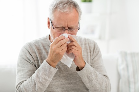 sick senior man with paper wipe blowing his nose Stock Photo