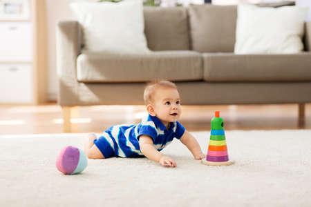Dulce bebé asiático con juguetes en casa