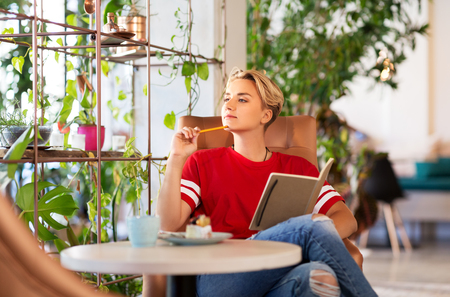 teenage girl with notebook at coffee shop or cafe