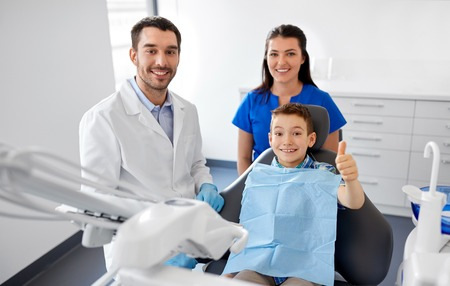 dentist and boy showing thumbs up at dental clinic