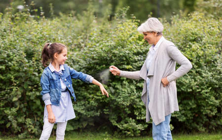 grandma and granddaughter with insect repellent Standard-Bild