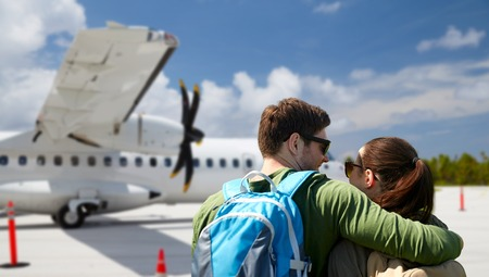 couple of tourists with backpacks over airplane