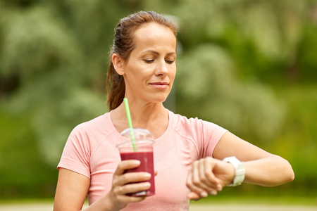 woman with smoothie looking at smart watch in park