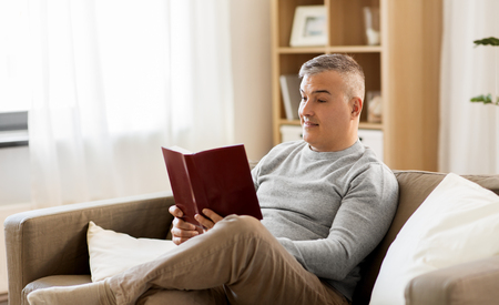man sitting on sofa and reading book at home Foto de archivo