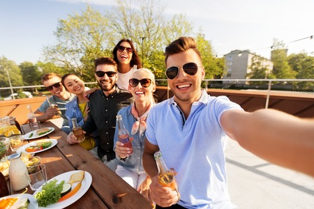 happy friends taking selfie at rooftop party Stockfoto