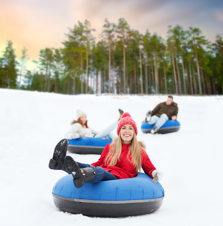 happy friends sliding down hill on snow tubes