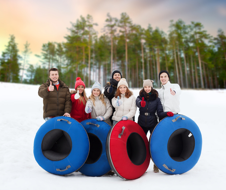 happy friends with snow tubes outdoors in winter Stock Photo