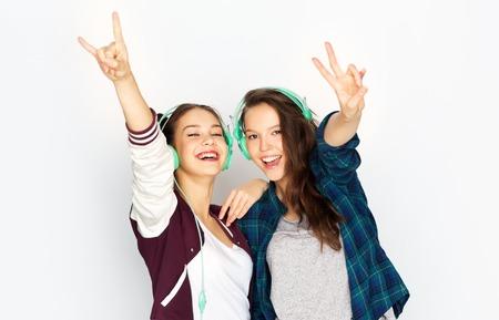 teenage girls in earphones listening to music
