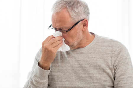sick senior man with paper wipe blowing his nose 版權商用圖片