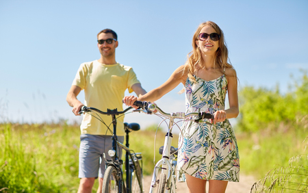 happy couple with bicycles on country road 스톡 콘텐츠 - 112286884