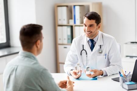 médico con glucómetro y paciente en el hospital Foto de archivo