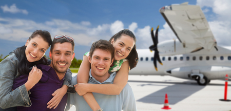 happy friends over plane on airfield background