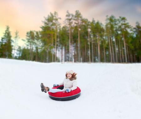 happy teenage girl sliding down hill on snow tube Stock Photo