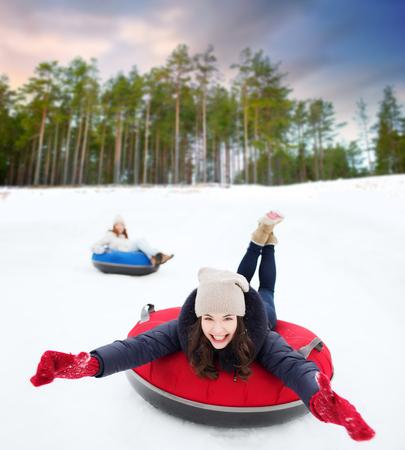 happy teenage girl sliding down hill on snow tube Reklamní fotografie