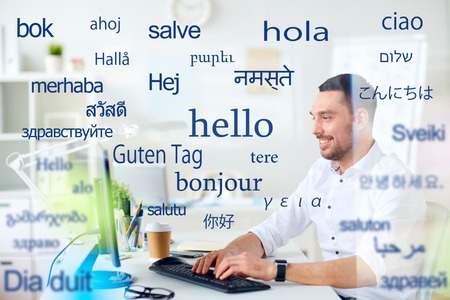 man with computer over words in foreign languages Stock Photo