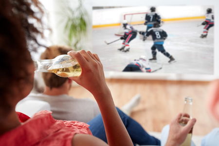 friends watching ice hockey and drinking beer