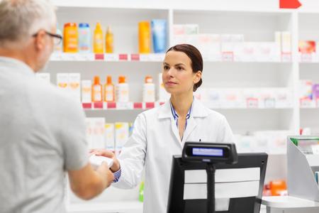 apothecary selling drug to senior man at pharmacy Foto de archivo