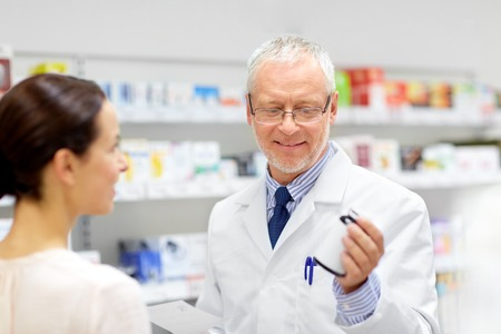 apothecary and woman with drug at pharmacy Stock Photo