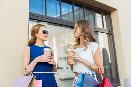 happy women with shopping bags and coffee outdoors Stockfoto