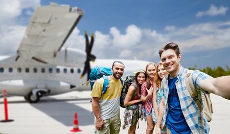 friends taking selfie over plane on airfield Banco de Imagens