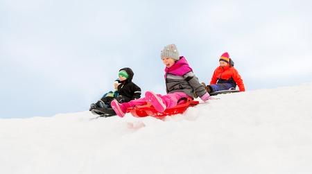 kids sliding on sleds down snow hill in winter 免版税图像