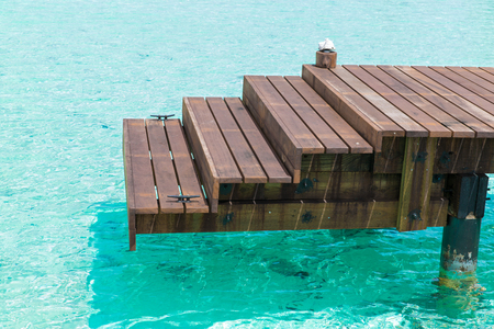 wooden pier with stair in sea water