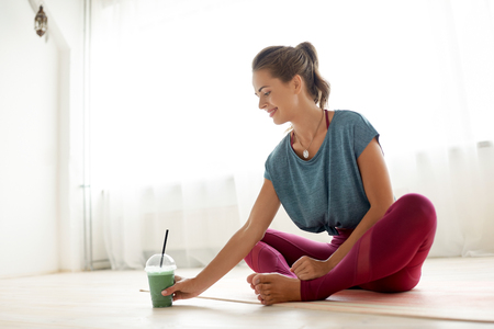woman with cup of smoothie at yoga studio Stockfoto