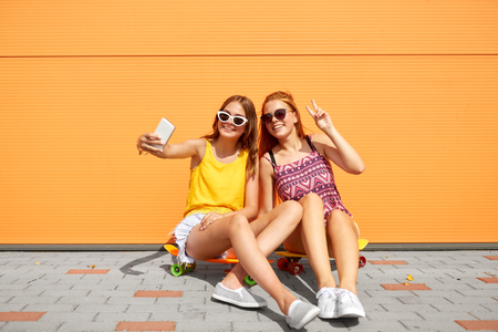 teenage girls with skateboards taking selfie 스톡 콘텐츠