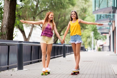 teenage girls riding skateboards in city 스톡 콘텐츠