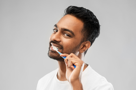 indian man with toothbrush cleaning teeth