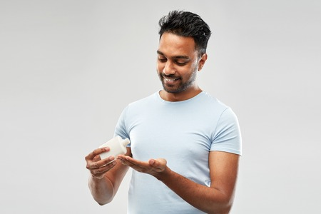 happy indian man applying lotion to his hand