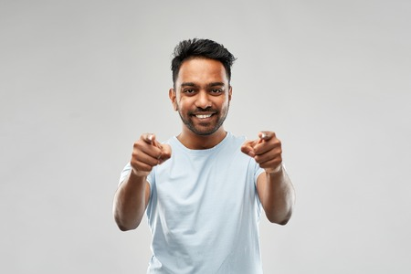 smiling indian man pointing fingers at you