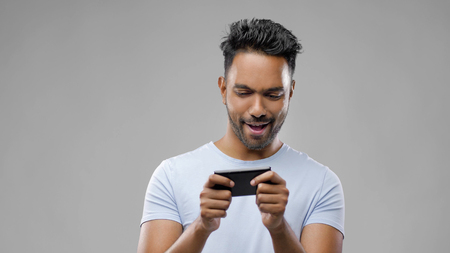 happy indian man playing game on smartphone Stockfoto