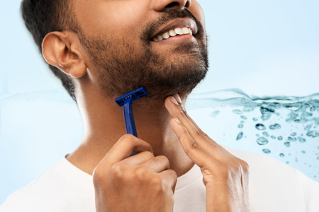 close up of man shaving beard with razor blade