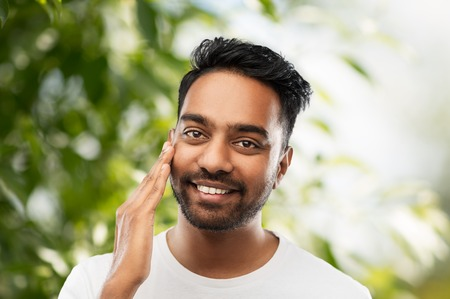 smiling indian man touching his face