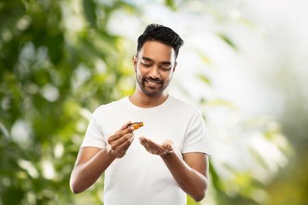 indian man applying grooming oil to his hand 版權商用圖片