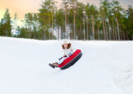 happy teenage girl sliding down hill on snow tube