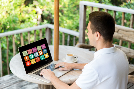 man with smart home icons on laptop computer Stock Photo
