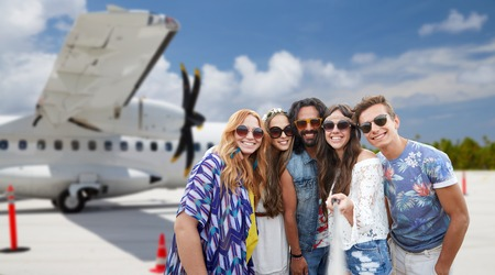 friends taking picture by selfie stick on airfield Фото со стока