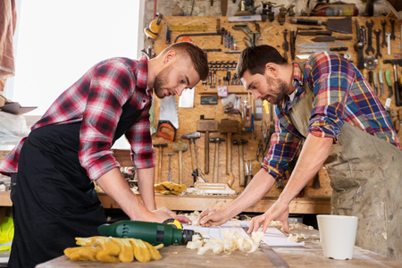 carpenters with ruler and blueprint at workshop Reklamní fotografie