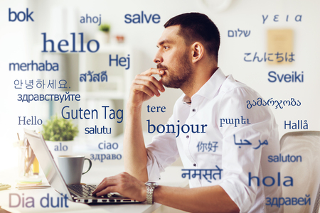 man with laptop over words in foreign languages Stok Fotoğraf