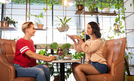 female friends drinking tea with cake at cafe Stock Photo