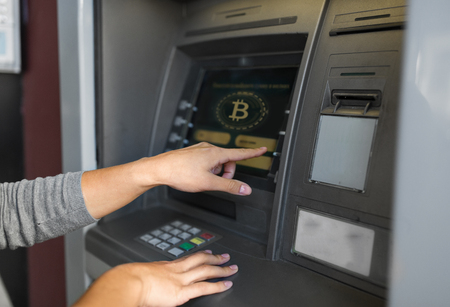 woman at atm machine with bitcoin icon on screen