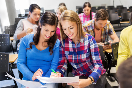 happy student girls with tests at lecture hall