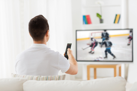 leisure, sport and entertainment concept - man with remote watching ice hockey game on tv at home from back