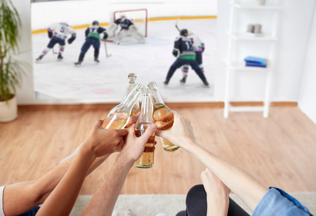 sport, entertainment and people concept - happy friends clinking beer bottles and watching ice hockey game on projector screen at home